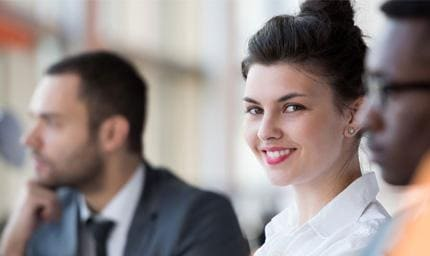 Smiling professional female with coworkers in the background