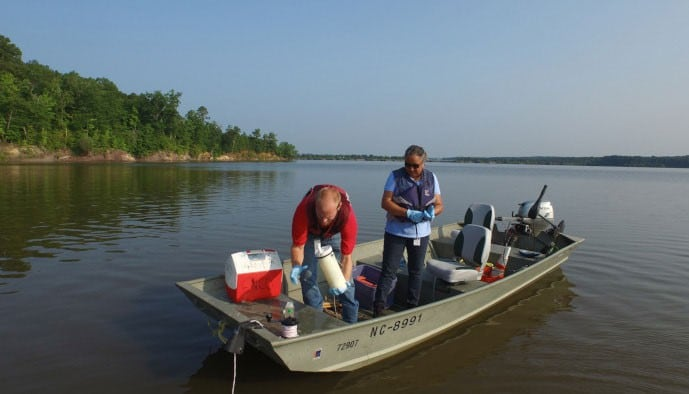 Travis Marion, left, and Michelle Woolfolk collect water samples at Falls Lake.