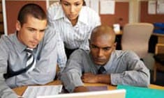 Three people looking at a computer