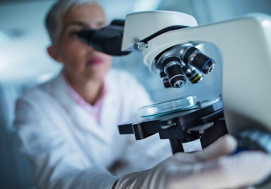 Woman looking through microscope